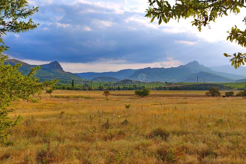 Un beau paysage de plaine avec une herbe défraîchie avec les pentes de montagne vertes sur la ligne d'horizon photo stock