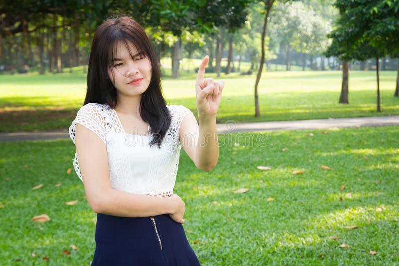 Un beau point asiatique de doigt d'action de jeune fille en vert de jardin photos stock