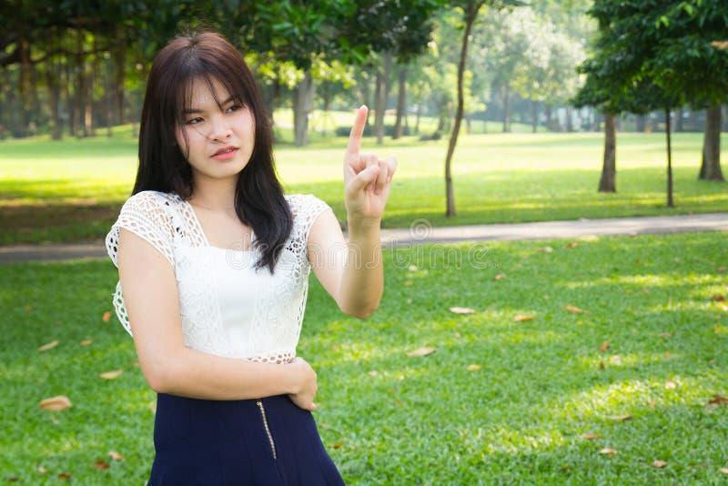 Un beau point asiatique de doigt d'action de jeune fille en vert de jardin images libres de droits