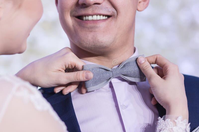 Un beau sourire d'un type dans un costume bleu, quand les mains du ` s de fille ajustent le noeud papillon gris images stock