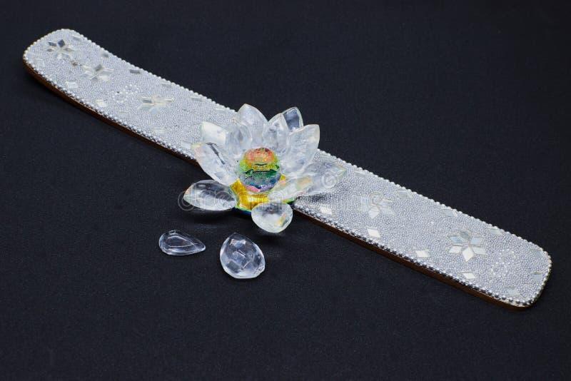 Un beau support d'encens avec les pierres lumineuses et fleur sur le fond noir photographie stock libre de droits