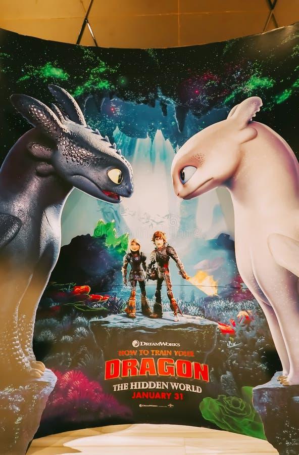 Un beau voyageur debout d'un film comment former votre affichage de Dragon Hidden World au cinéma pour favoriser le film photo stock