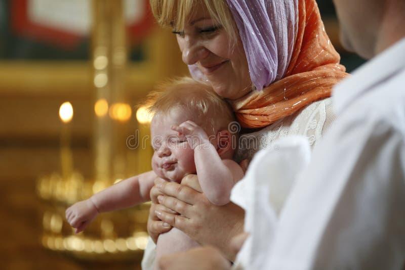 Un bebé bautizado por la mamá en sus brazos fotos de archivo