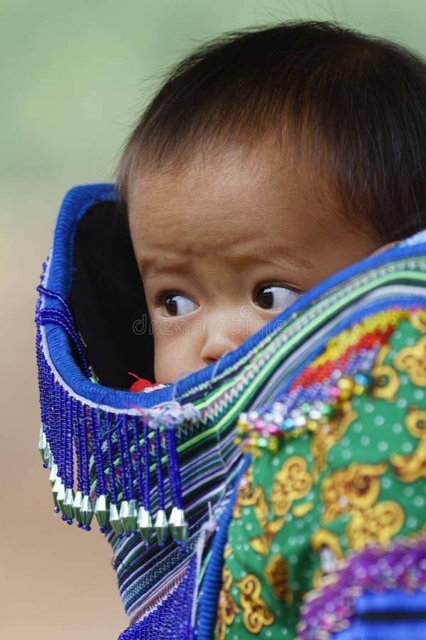 Un bebé curioso en una cesta imagen de archivo