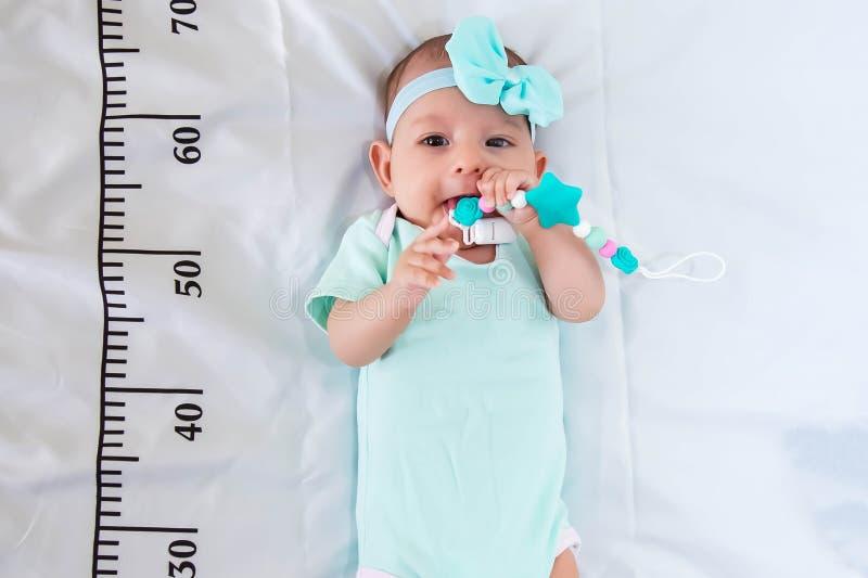 Un bebé de tres meses en la ropa del verde menta que miente en una cama en la cual una regla de medición para el crecimiento se d imágenes de archivo libres de regalías