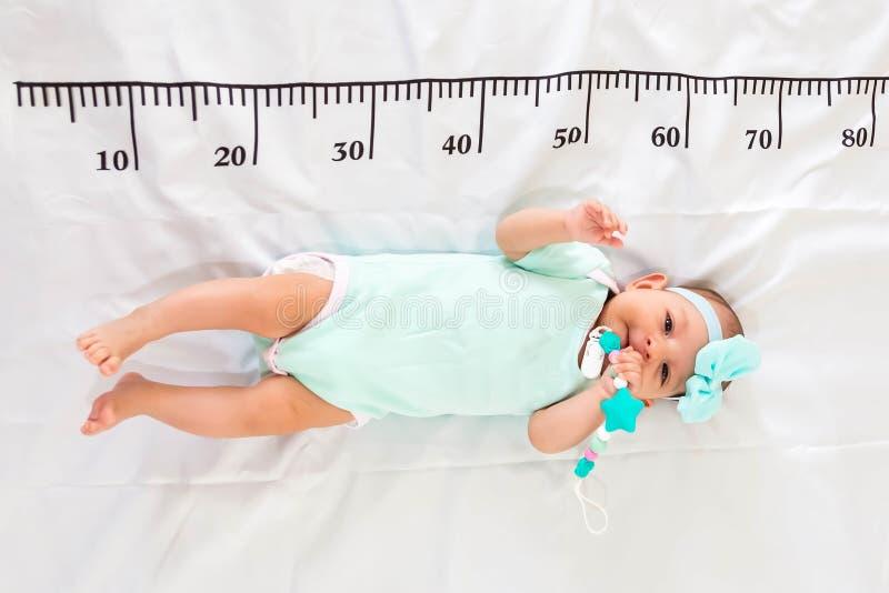 Un bebé de tres meses en la ropa del verde menta que miente en una cama en la cual una regla de medición para el crecimiento se d imagenes de archivo