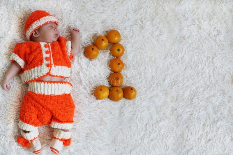 Un bebé del mes Bebé recién nacido durmiente de un mes en naranja fotografía de archivo