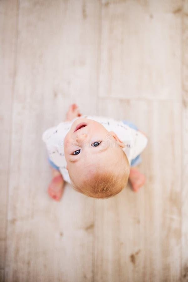 Un bebé en el piso en casa, mirando para arriba Copie el espacio imagen de archivo