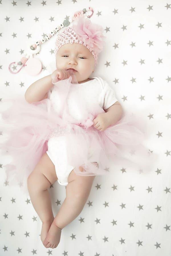 Un bebé en la mirada blanca del lecho en casa agradable aprendizaje recién nacido fotografía de archivo libre de regalías