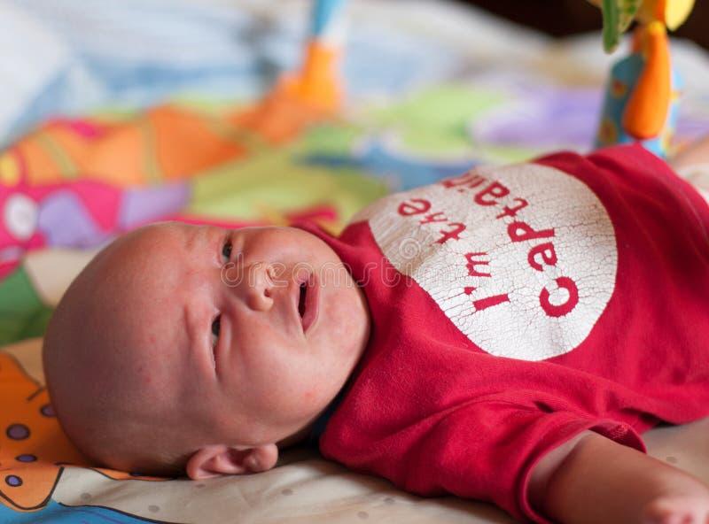 Un bebé en una camiseta roja que llora en un pesebre imagenes de archivo