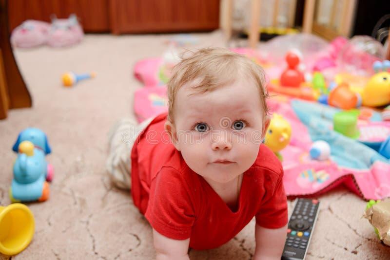 Un bebé es que juega y de mirada de la cámara fotos de archivo