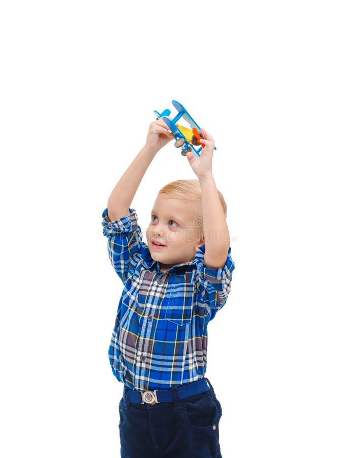 Un bebé fascinador que juega con un aeroplano del juguete que lo levanta alto para arriba Aislado en blanco fotos de archivo