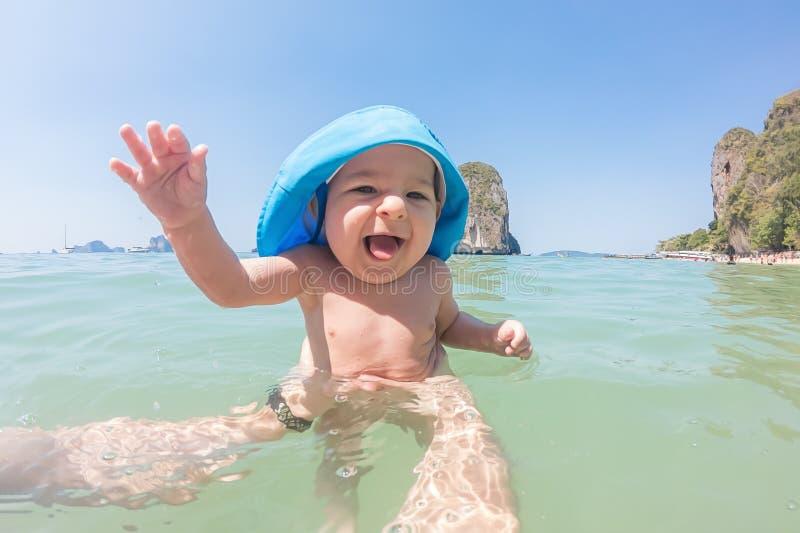 Un bebé feliz de siete meses se baña en el mar por primera vez El día soleado, papá detiene al bebé Solamente manos del hombre fotos de archivo
