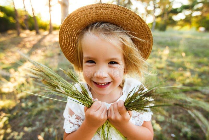 Un bebé lindo en un sombrero de paja y un vestido del blanco se está sentando en la hierba fotografía de archivo