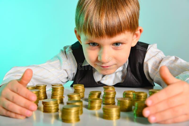 Un bebé lindo está abrazando sus monedas del dinero fotografía de archivo libre de regalías