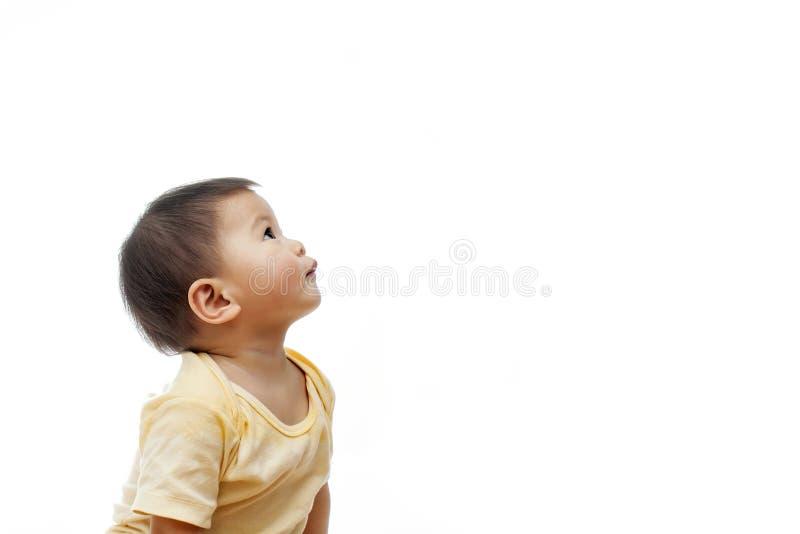 Un bebé mira para arriba con la ropa amarilla, no considerando la cámara, aislada el blanco imagen de archivo