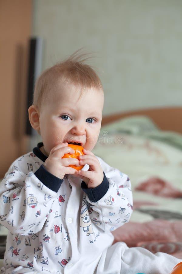 Un bebé que come la fruta foto de archivo