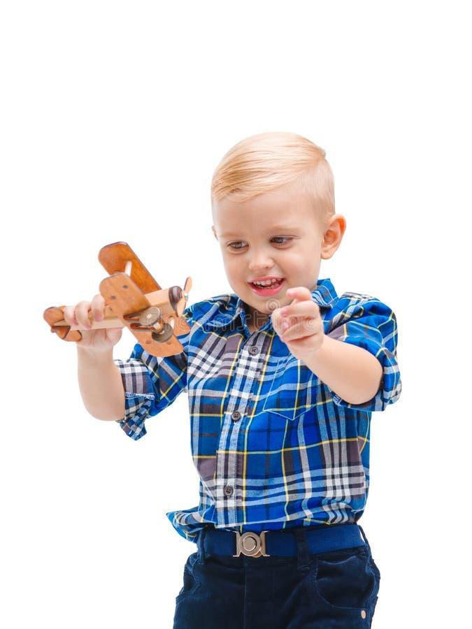 Un bebé que juega con un aeroplano del juguete Aislado en blanco imágenes de archivo libres de regalías