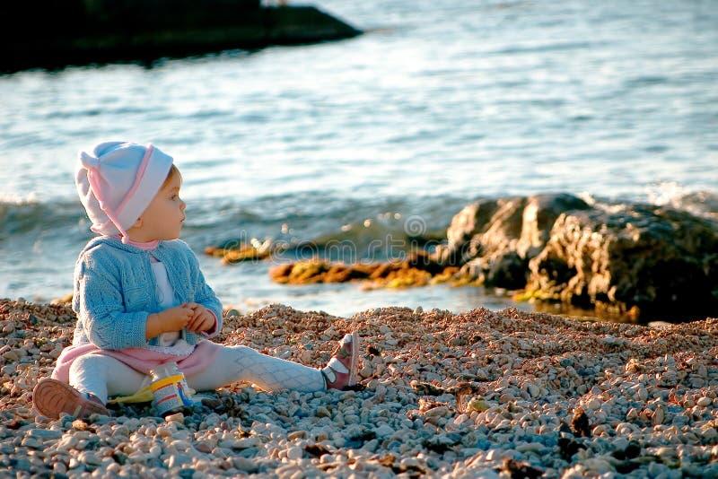 Un bebé que se sienta cerca del mar foto de archivo libre de regalías