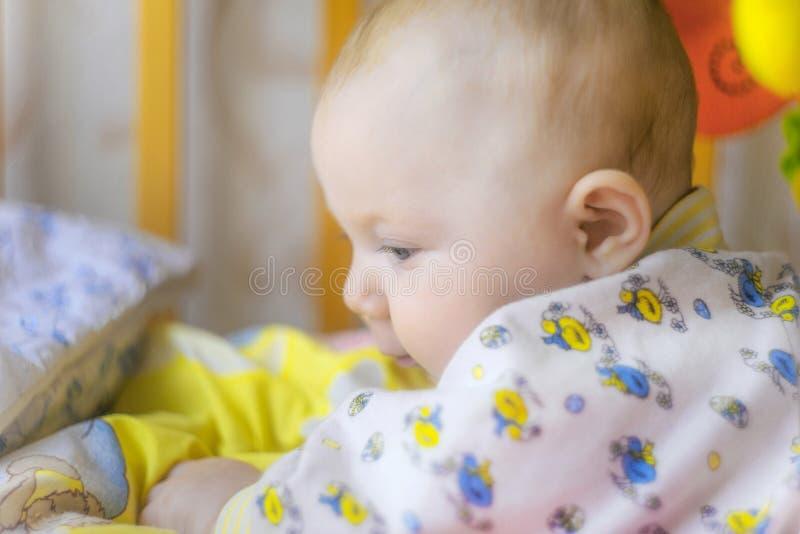 Un bebé recién nacido está mintiendo en un pesebre y está jugando con los juguetes, primer foto de archivo