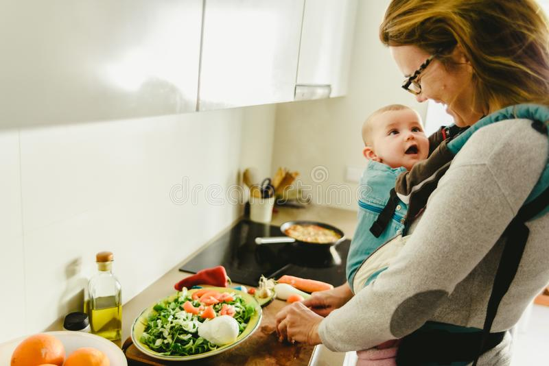 Un bebé sonriente portado en una mochila portadora de bebés mirando a su madre mientras ella cocina, concepto de conciliación fam foto de archivo libre de regalías