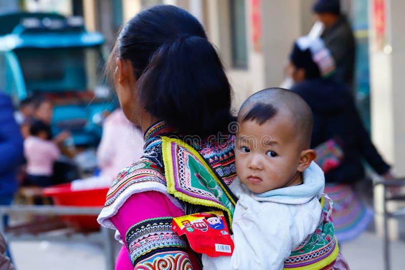 Un bebé, y en el fondo una mujer, en ropa típica en un pueblo en Yunnan meridional, China Yunnan, China foto de archivo libre de regalías