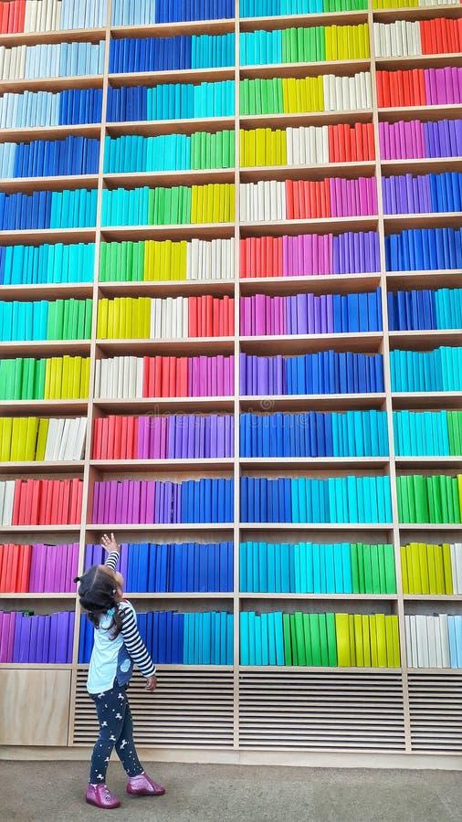 Un beb? joven en la situaci?n de la biblioteca cerca de un estante sin fin con la fila colorida de libros fotos de archivo