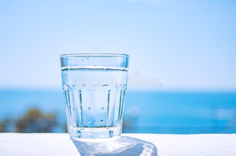 Un becher en verre rempli de supports clairs de l'eau sur une plage sablonneuse par la mer Style de vie sain images libres de droits