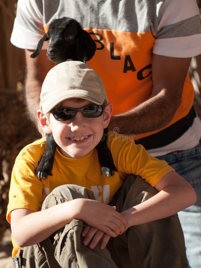 Un beduino en una camiseta negra guarda una cabra negra alrededor de su cuello como muchacho turístico fotos de archivo libres de regalías