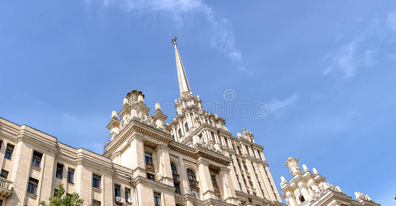 Un bel édifice haut, un gratte-ciel de Stalin sur le fond d'une partie du bâtiment de l'hôtel de l'Ukraine contre le s bleu photographie stock libre de droits