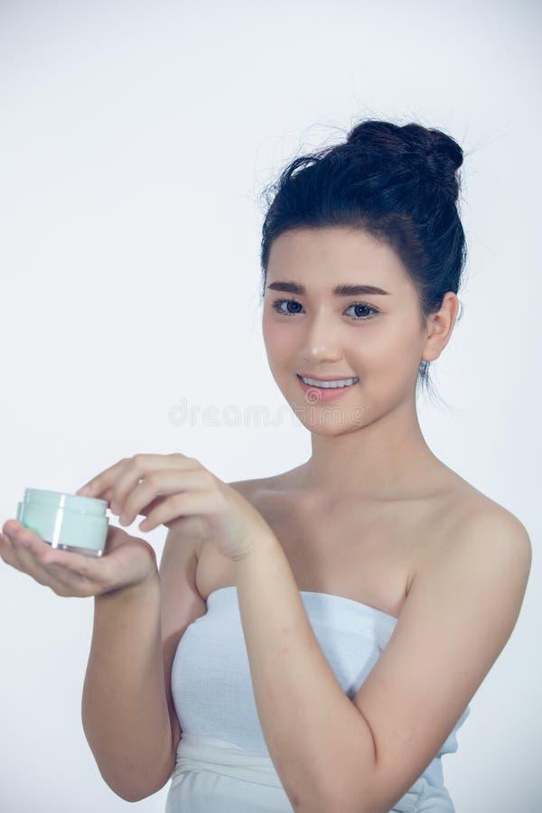 Un bel Asiatique de femme employant un produit de soin pour la peau, une cr?me hydratante ou une lotion prenant soin de son teint photo libre de droits