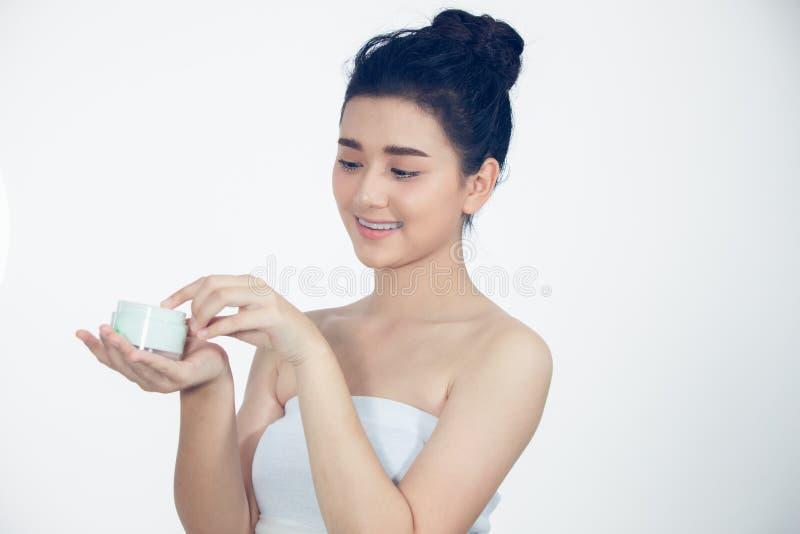 Un bel Asiatique de femme employant un produit de soin pour la peau, une cr?me hydratante ou une lotion prenant soin de son teint photo stock