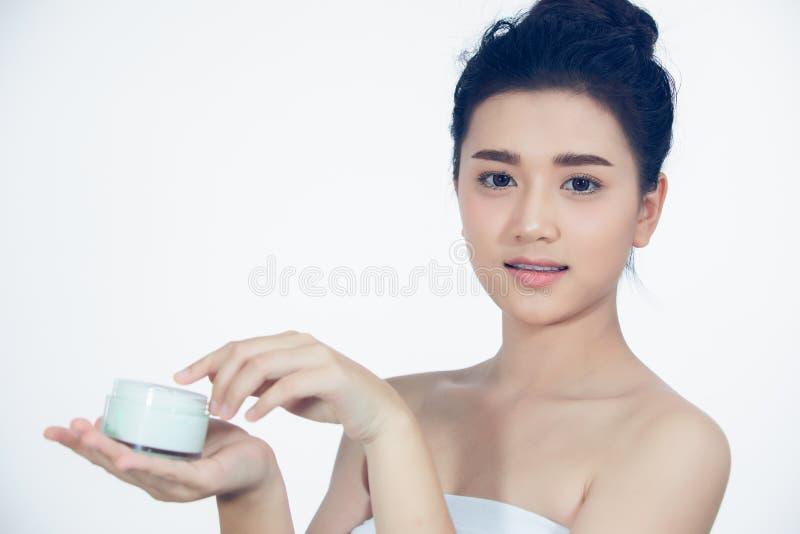 Un bel Asiatique de femme employant un produit de soin pour la peau, une cr?me hydratante ou une lotion prenant soin de son teint photographie stock libre de droits
