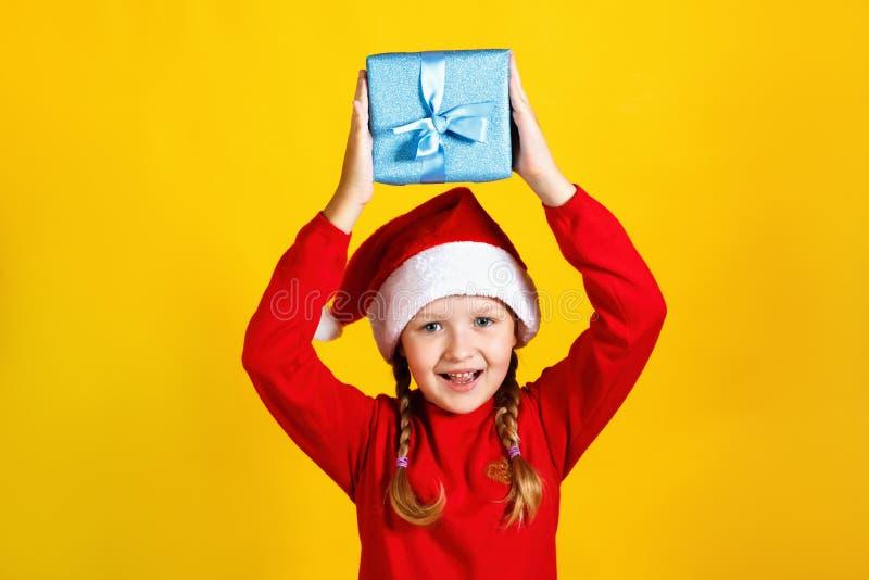 Un bel bambino tiene una scatola sopra la sua testa Una bambina a santa claus cappello con Natale presente in giallo immagine stock libera da diritti