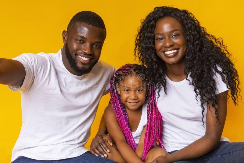 Un bel padre nero che si fa il selfie con la figlia e la moglie. immagine stock libera da diritti