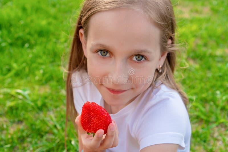 Un bello bambino con gli occhi verdi tiene le fragole nelle suoi mani e sorrisi immagine stock