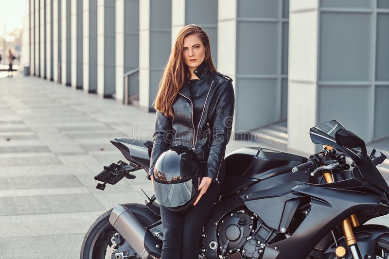 Un bello casco della tenuta della ragazza del motociclista mentre appoggiandosi il suo superbike fuori di una costruzione fotografia stock libera da diritti