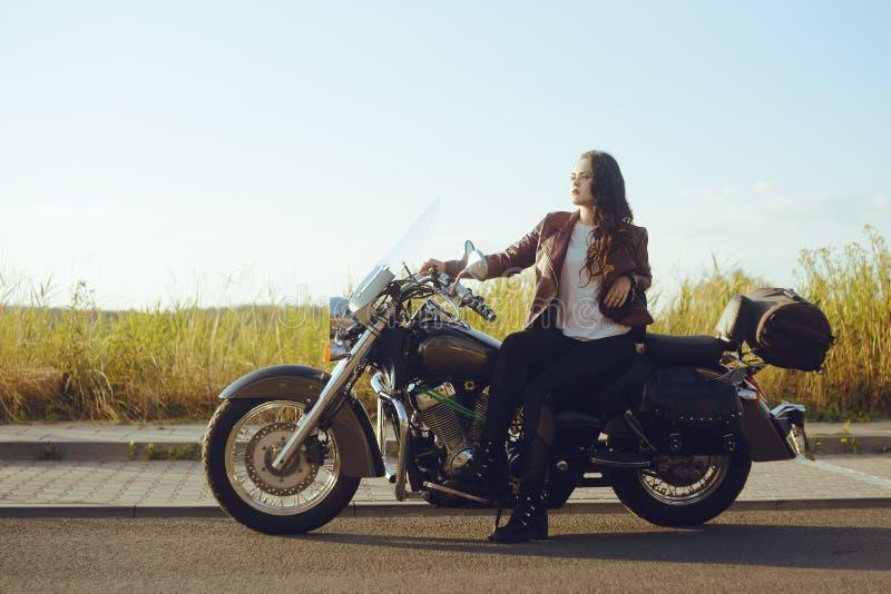 Un bello castana in un bomber rosso sta stando vicino ad un motociclo nel campo Ragazza su un motociclo La ragazza al tramonto immagine stock libera da diritti