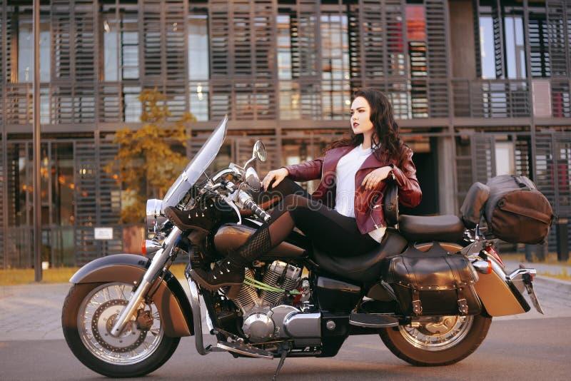 Un bello castana sta sedendosi su una bici vicino all'ufficio La ragazza è venuto a lavorare ad un motociclo Successo Ragazza Lez immagine stock