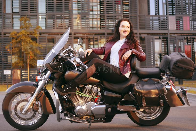Un bello castana sta sedendosi su una bici vicino all'ufficio La ragazza è venuto a lavorare ad un motociclo Successo Ragazza Lez immagini stock