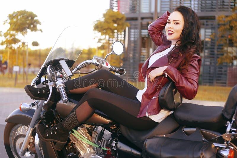 Un bello castana sta sedendosi su una bici vicino all'ufficio La ragazza è venuto a lavorare ad un motociclo Successo Ragazza Lez fotografia stock libera da diritti