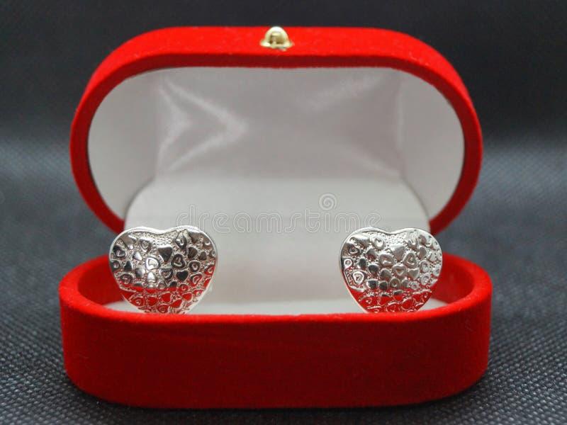 Un bello cofanetto rosso dell'anello con due cuori d'argento immagini stock