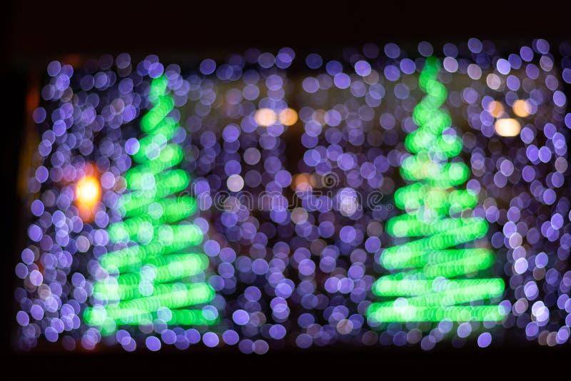 Un bello fondo di Bokeh di due alberi di Natale e di luci porpora fotografie stock libere da diritti