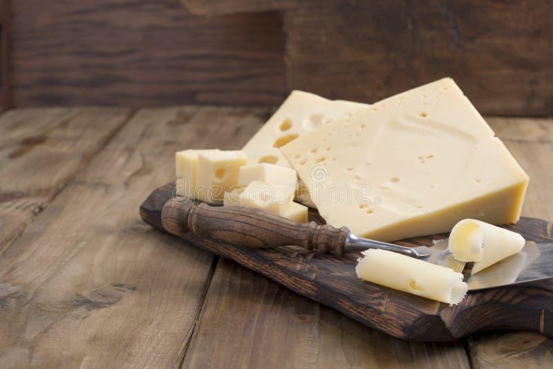 Un bello formaggio svizzero con i fori, un prodotto lattiero-caseario utile Alimento saporito Foto stile country Posto per testo  immagine stock