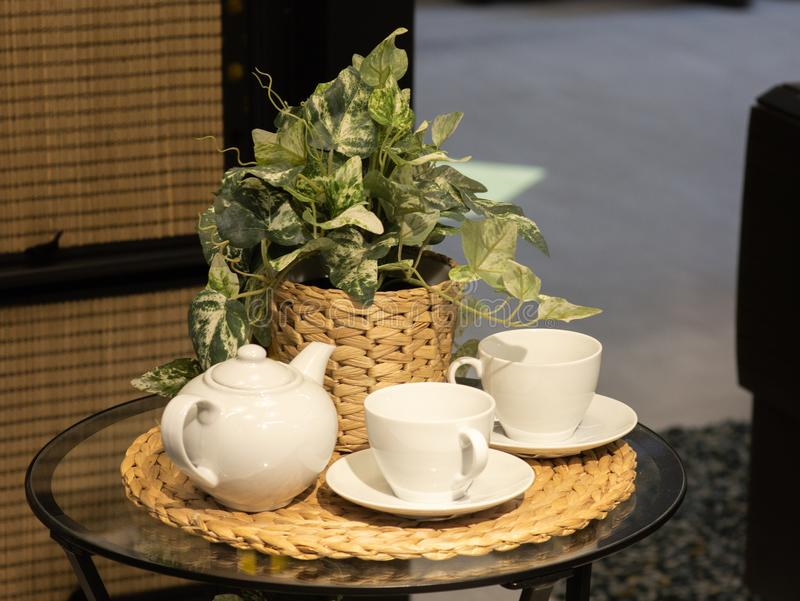 Un bello insieme di bianco di due ciotole e di una teiera, nei precedenti un fiore fotografie stock