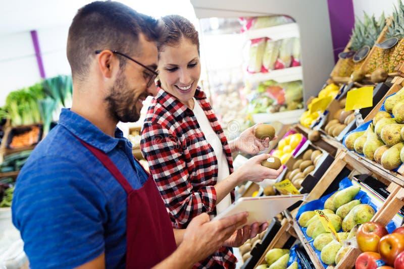 Un bello inventario facente di due giovani venditori con la compressa nel fruitshop immagine stock libera da diritti