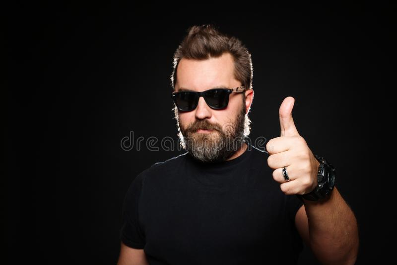 Un bello, l'uomo forte con un'acconciatura alla moda e la barba mostrano il pollice su nello studio su un fondo nero con lo spazi fotografie stock libere da diritti
