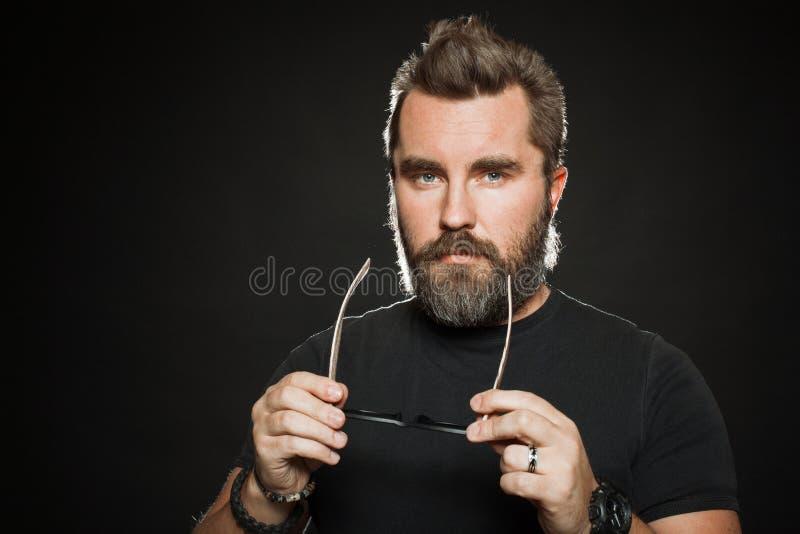 Un bello, l'uomo forte con un'acconciatura alla moda e la barba vestono gli occhiali da sole nello studio su un fondo nero Con lo fotografie stock