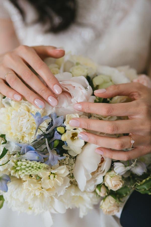 Un bello manicure beige delicato della sposa di eleganza in lei armi Mani su un mazzo bianco di nozze immagini stock libere da diritti