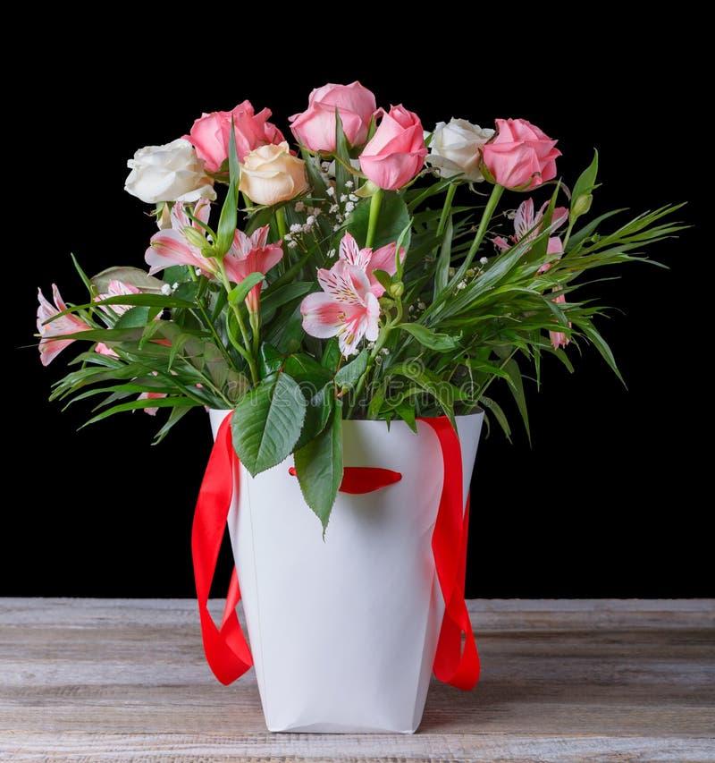 Un bello mazzo dei fiori in una scatola bianca con un nastro rosso su una tavola di legno Su un fondo nero fotografia stock